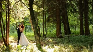 bride and groom embracing in forest