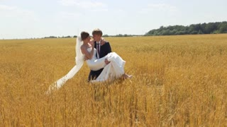Bride and groom have a fun on the wheat field