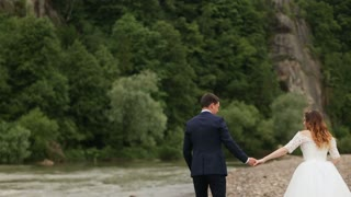 Bride and groom holding hands near the river