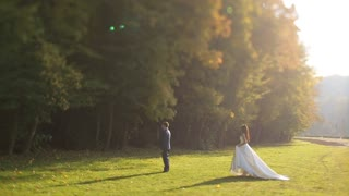 Bride and groom in love looking at each other at beautiful green forest