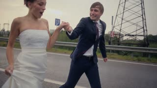 Bride and groom running at the rain