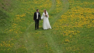 Bride and Groom walking together in flower field.