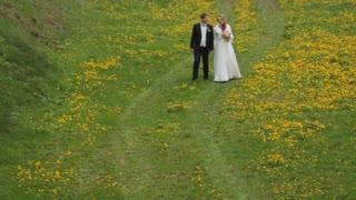 Bride and Groom walking together in flower field.