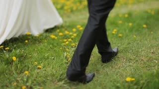 Bride and Groom walking together in flower field