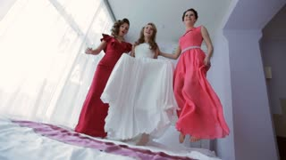 bride jumping on the bed with bridemaids. The bride to have fun in the hotel room. The bride in a white dress.