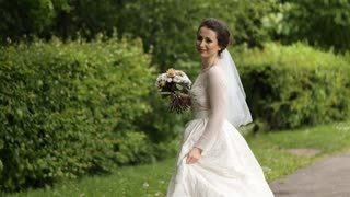 Bride smilling with the bouqet in the park