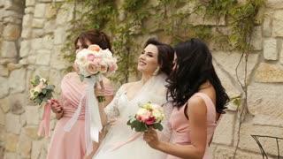 Bride with her friends handing bouqet