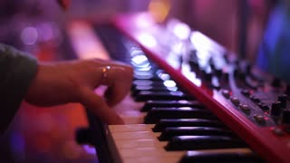 close up shot: Man musician playing electric piano on stage at a concert.