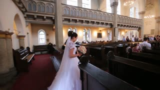 Elegant smiling bride in white dress and veil and groom wearing suit holding hands walking through old church