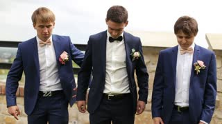 Groom and his friends are buttoning the jackets