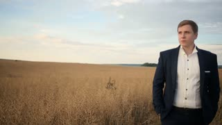 Groom is walking at the wheat field