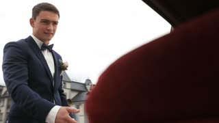 Groom opens and holds the car door for the beautiful young bride