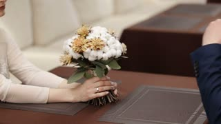 Hands of couple and wedding bouquet