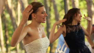 Happy bride and guests are dancing