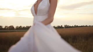 Happy bride dancing near her groom at the wheat field