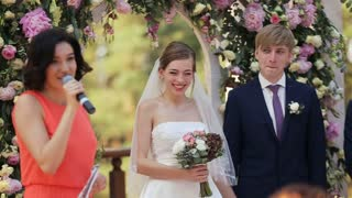 Happy wedding couple is standing near decorated with flowers arch