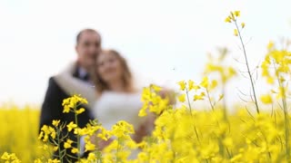 Husband and wife in wedding dress and suit smiling and standing among yellow flowers.