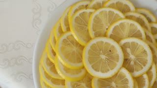 Juicy lemon with slices on plate rotating, top shot