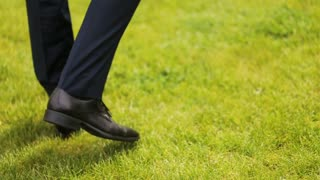 Legs of the groom in the blue pants on the green grass