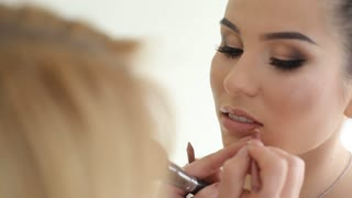 Makeup artist paints lips for girl. Professional make-up of model. Beautiful bride's makeup