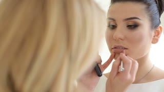 Makeup artist paints lips for girl. Professional make-up of model. Beautiful bride's makeup