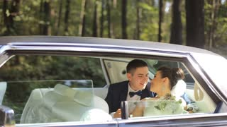 man and woman in wedding dresses sit in limousine together