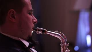 man playing saxophone dark background music backlit silhouette