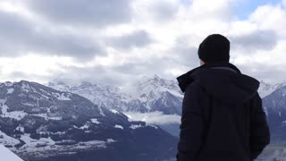 man shot clouds and mountains on the camera/dslr . Switzerland, the top of the mountain. beautiful cloudy weather. shot the man behind, he in the hood and leather jacket, face is not visible