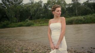 Pretty bride standing near the river