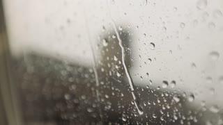 Rain running down window close up