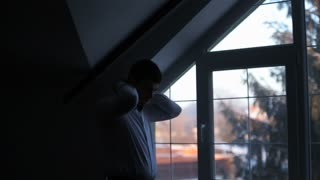 Silhouette of a businessman wears a shirt front of the window