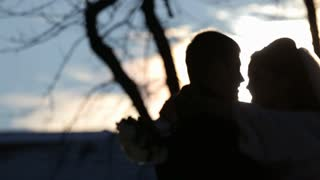 silhouette of bride hugs and kisses groom with bouquet round his neck against sun rising,