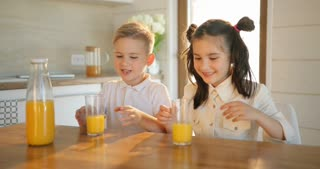 A beautiful girl and boy drinking fresh juice at home. Kids drinking juicy smoothie. Healthy life concept, copy space.