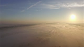 Aerial view of the city shrouded in thick fog hot air balloon on the sunrise.