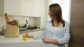 Atractive young woman drinking orange juice in the kitchen.