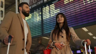 Atracttive young business couple in love with baggage looking at timetable departure board at international airport