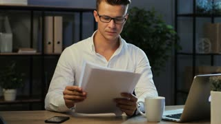 Attractive business man in casual shirt checking the finance report on the office background.