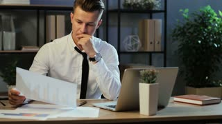 Attractive business man in casual shirt checking the finance report using laptop on the office background.