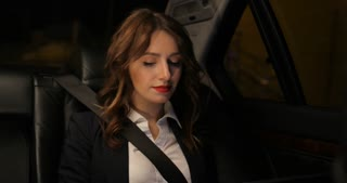 Attractive businesswoman works at a laptop in car with city at night light