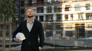 Attractive caucasian business man in shirt and black suit standing on unfinished construction territory, putting on head the white helmet. Outdoor.