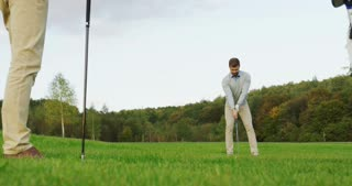 Attractive caucasian man playing golf on the pitch. Golf club on the first plan. Outside