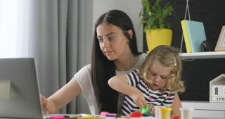 Attractive caucasian young woman with black long hair working on laptop while her dauther opening box with plasticine at home. Indoor.