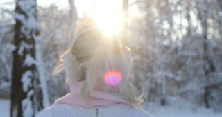 Attractive girl wearing a winter white pullover and pink scarf goes down the winter park, sun is shining, than turns to camera and smiles. Woman enjoying snowfall, expressing positivity