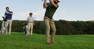 Attractive golf player with beard and in glasses hitting a ball with a club and his friends with golf bags watching him on a background. Good sunny weather day. Outside