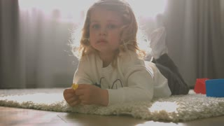 Attractive little girl with blond curly hair lying on the floor and playing the toy on living background. Indoor.