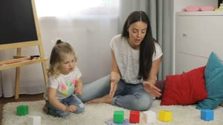 Attractive little girl with blond curly hair siting on the floor in home with her mother and playing with cubes. Indoor.