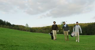 Attractive male golf players walking with their clubs and golf bags on the golf pitch to start a game, talking and laughing. Outside