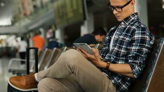 Attractive man in the glasses using tablet for the chatting while sitting in the airport lounge. Side view.