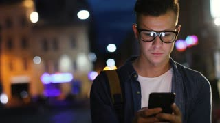 Attractive man in the stylish glasses using smart phone in the street at the evening time on the light background of the bulding.