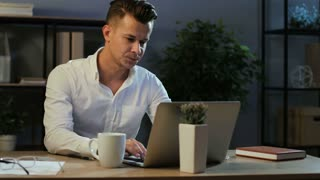 Attractive young business man in classic shirt try working with anoying head ache in the laptop in the stylish office at the evening.